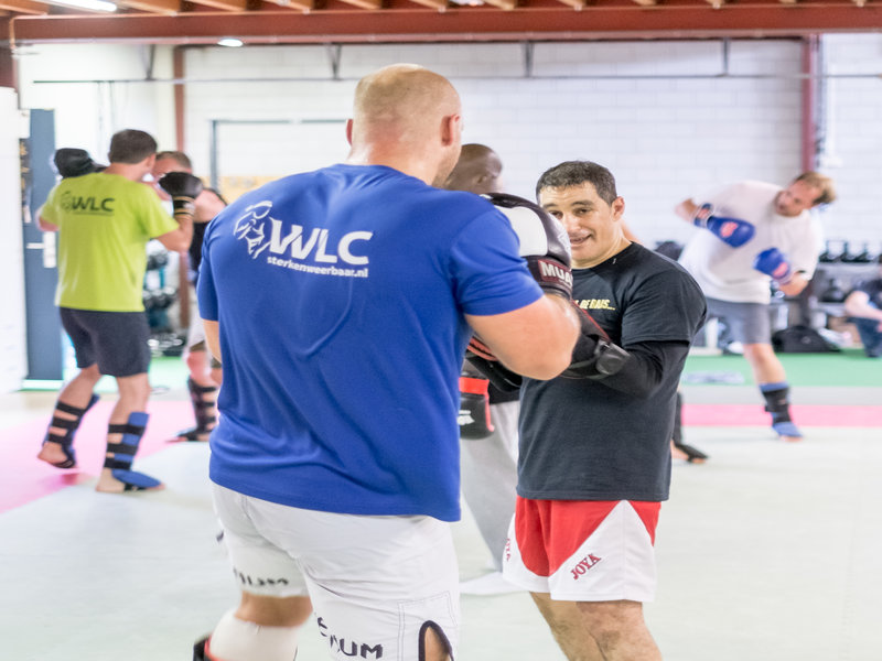 kickbokstrainer legt technieken uit tijdens de training
